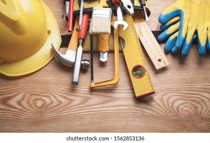 Work tools with helmet and gloves on wooden background.
