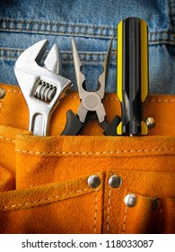 Work tools in orange tool bag with jeans.