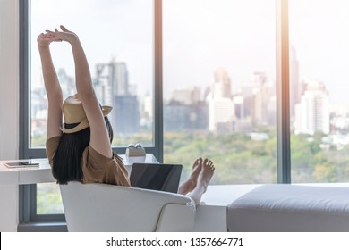 Work and travel lifestyle relaxation and healthy work-life balance with young freelancer Asian working woman take it easy happily resting in comfort luxurious hotel guest room with peace of mind