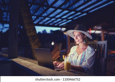 Work and travel. Study and vacation. Working outdoors. Freelance concept. Pretty young woman using laptop in tropical beach bar cafe.