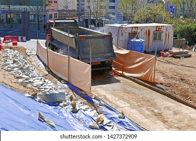 a work truck washing wheels at an apartment construction site.