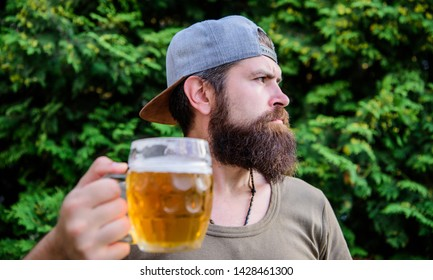 I work until beer oclock. Bearded man drinking beer outdoors. Hipster enjoying beer in summer. Brutal man with beer mug. Drinker relaxing with alcoholic drink on nature.