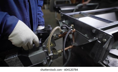Work using mechanized hand for spot welding of metal izdeliy.Muzhchina working in a factory with a metal, its duty spot welding and soldering. Technology department