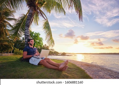 Work and vacation. Young man working on laptop computer on the tropical beach under the palm tree.