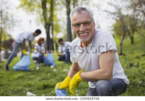 Arbeiten Sie als Freiwilliger. Erfahrener Senior-Freiwilliger, der Mülltüte hält und mit der Kamera starrt