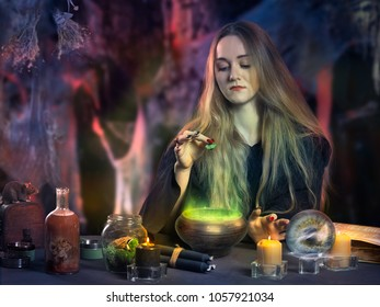 The work of the witch. Young beautiful witch making potions using magical ingredients and spells