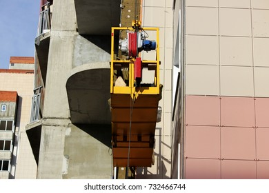 work with yellow front two suspended cradle with workers on a newly built high-rise building.
