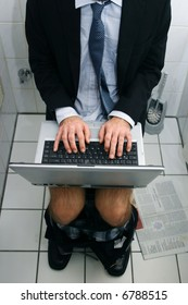 workaholic business man working on his lap top while using the toilet
