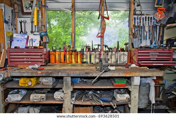 A workbench in a stereotypical manly sort of shed where lots of tools are sorted into containers and stored on shelving, hanging on hooks and along the window ledge.