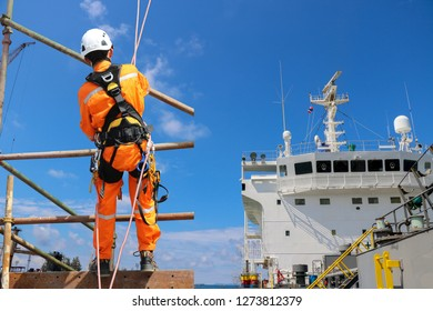 Worker abseiling from high places on the high scaffolding wear equipment protective safety harness on structure site project and shipyard on accommodation bridge deck of cargo ship background.