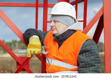 Worker with Adjustable wrench near metal structures