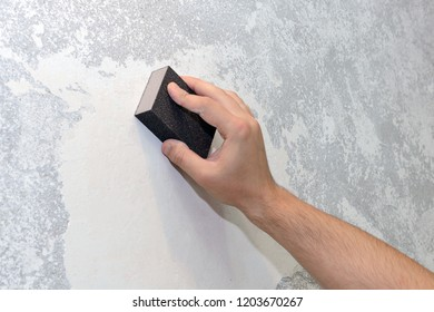 worker aligns the sandpaper wall