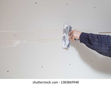 Worker aligns the walls with plaster. Repair in the house.