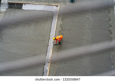 Worker alone yellow hat, orange suit.