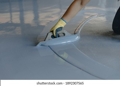 The worker applies gray epoxy resin to the new floor - Shutterstock ID 1892307565