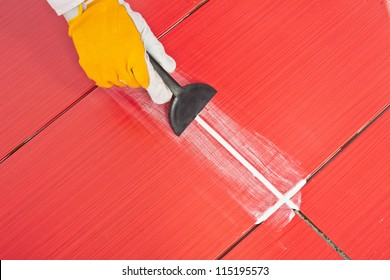 worker applies  grout whit rubber trowel red tiles