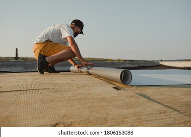 Worker applies pvc membrane roller on roof very carefully