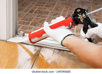 Worker applies silicone caulk on the wooden floor for sealant waterproof