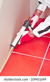 worker applies silicone sealant with gun on corner wall tiles