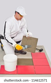 Worker Applies with Trowel Tile Adhesive on a Floor Red Tile