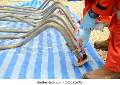 Worker are apply the penetrate to the welding of stainless steel pipe with a brush for finding the defect. This is first step of penetration testing (PT).