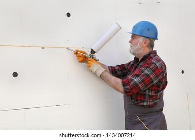 Worker applying adhesive glue to styrofoam, polystyrene thermal insulation of wall using applicator gun
