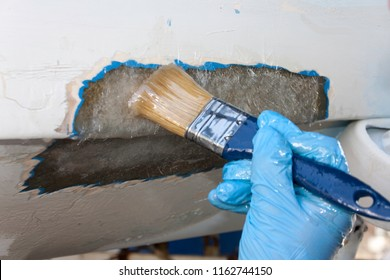 A worker is applying epoxy to polyester pach