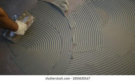 worker applying tile adhesive glue on the floor