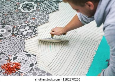 worker applying tile adhesive on the floor