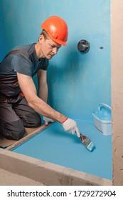 The worker is applying waterproofing paint to the floor in the bathroom.