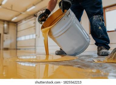 Worker applying a yellow epoxy resin bucket on floor. - Shutterstock ID 1825562213