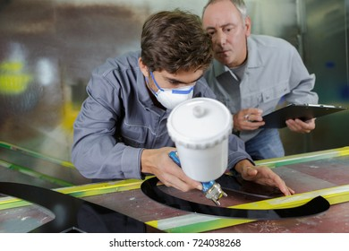 worker and apprentice learning to spray painting