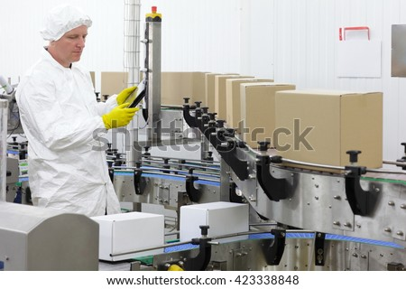 worker in apron, cap with tablet, at production line in factory