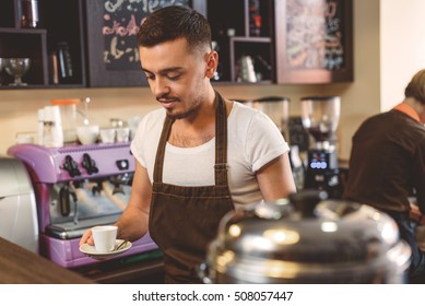 worker in apron holding a cup of coffee in the kitchen