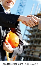 Worker and architect shaking hands at construction site