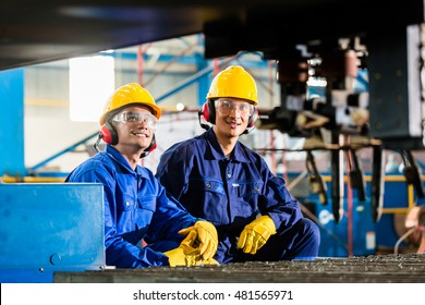Worker in Asian factory at industrial metal cutting torch machine