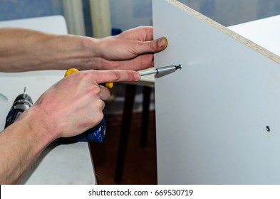 Worker assemble chipboard furniture with the screwdriver