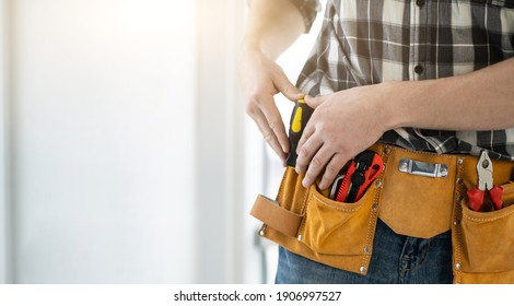 Worker assembler with tool belt full of instruments, copy space