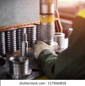 The worker assembles the pressing of the bearing into a metal clip on the machine, assembles the finished unit, close-up, factory