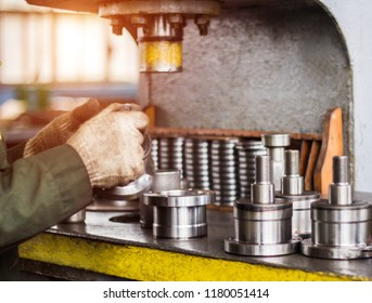 The worker assembles the pressing of the bearing into a metal clip on the machine, assembles the finished unit, close-up, press