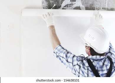 worker attaching wallpaper to wall