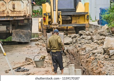 Worker and backhoe work in wet site
