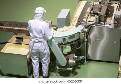 worker behind the conveyor in shop of confectionery factory