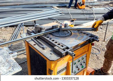 The worker is bending rebars with rebar bending machine in the site. The most common type of rebar is carbon steel, typically consisting of hot-rolled round bars with deformation patterns.