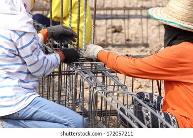 worker bending steel for construction job