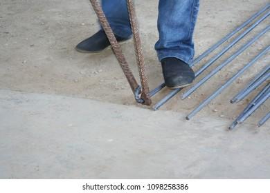 Worker bending steel with steel bending equipment by hand
