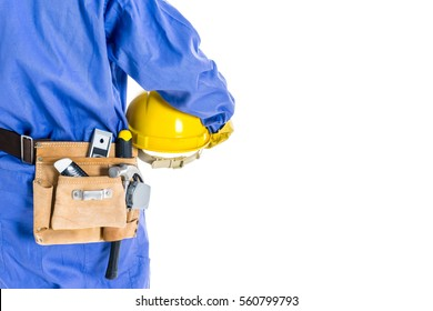 Worker with blue coverall holding yellow hard hat and leather tools bag at waist with white background.