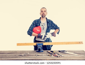 worker in blue plaid  shirt with red helmet on workbench