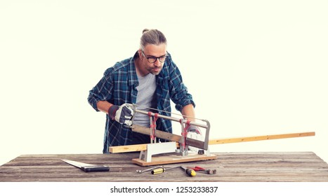 worker in blue plaid  shirt sawing wood