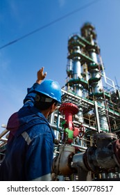 Worker in the blue uniform and blue helmet and grey distillation column at the oil refining plant on the blue sky.